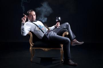 Mann in Wohlstand auf Hocker lässig sitzend