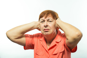 Old woman covering her hands over her ears, loud sound