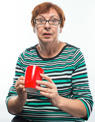 old woman holding a red cup of coffee (tea)
