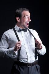 Mann mit Hosenträger blickt auf leere Fläche und lacht