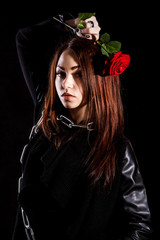 Beautiful young woman with chains and a red rose