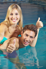 Couple in swimming pool holding thumbs up