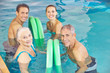 Two couples in aqua fitness class in swimming pool