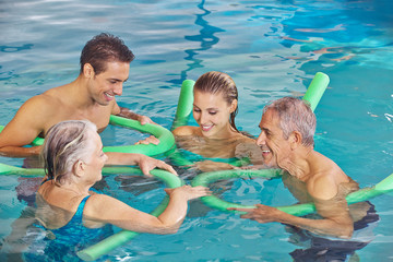 Family with senior couple in water of pool