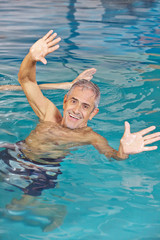 Elderly man playing water ball in swimming pool
