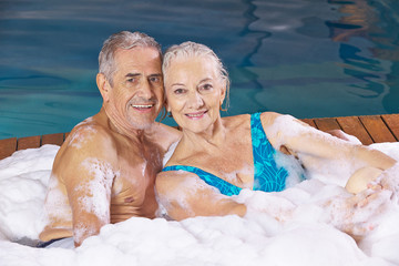 Senior couple taking foam bubble bath