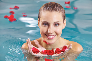 Woman relaxing in pool with petals of roses