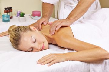 Woman receiving nape massage in spa