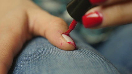 Young woman coloring her nails with red nail polish