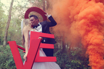 Bride and groom holding big LOVE letters in the forest