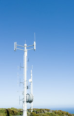 Mobile Communications tower against clear blue sky.