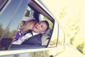 Bride and groom having fun in the car