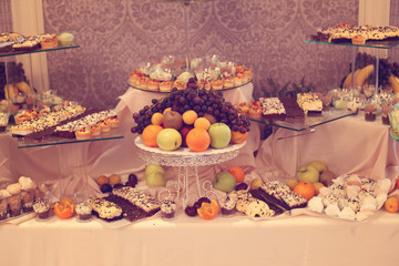 Table with delicious fruits and desserts
