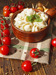 dumplings with meat on a wooden table with tomatoes and onions