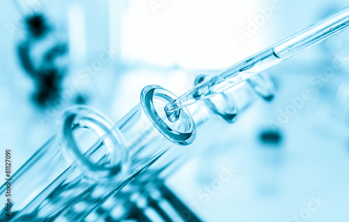 Pipette adding fluid to one of several test tubes . - 81127091