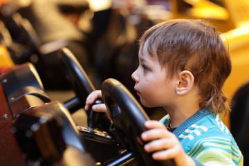 Boy at the wheel of car simulator