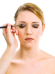Applying makeup on beautiful model