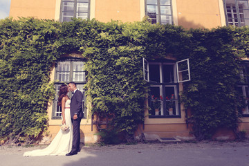 Bride and groom embracing in front of a beautiful house