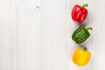 Colorful bell peppers on wooden table
