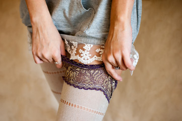 Tender undressing.  Girl in nightdress moving down her tights