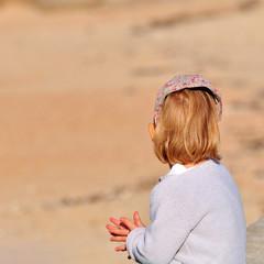 Petite fille en pleine réflexion regardant une plage