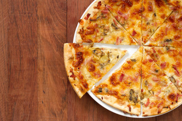 pizza on white plate on brown background