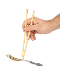 Hand with chopsticks and fork