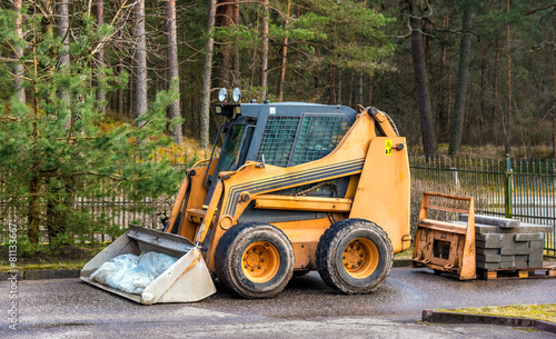 Bobcat or skid loader parked in forest - 81133667