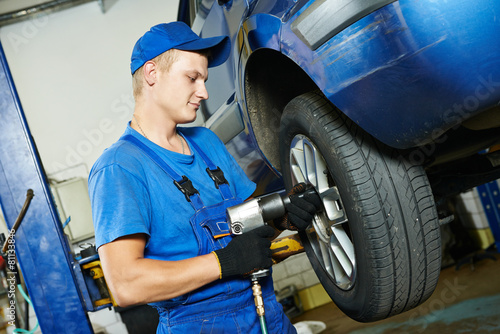 mechanic screwing car wheel by wrench - 81133846