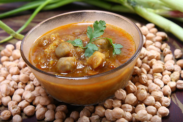 indian spicy chana masala with raw chickpeas and green onion