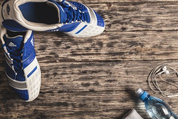Running. Sport equipment. Sneakers, water, earphones and phone