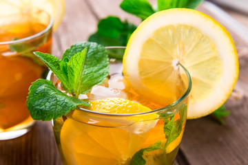 Lemonade with fresh lemon and mint on wooden background