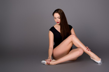 Young female contortionist in black bodysuit on dark background