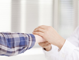 Doctor hands comforting his female patient at the clicic