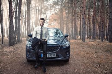 Attraktiver Geschäftsmann sitzt auf der Motorhaube