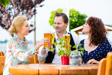 Freunde prosten mit Bier im Biergarten