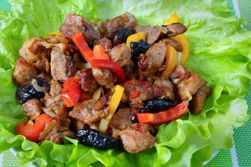 Мясо с черносливом и болгарским перцем на листьях салата