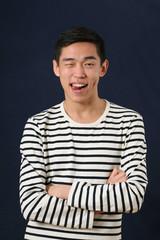 Funny young Asian man showing his tongue and looking at camera