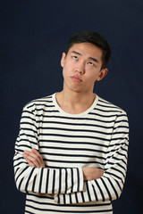 Frustrated young Asian man with crossed hands rolling eyes up