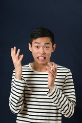 Displeased young Asian man gesturing with two hands and looking