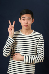 Young Asian man giving the victory sign and looking at camera