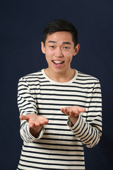 Smiling young Asian man gesturing with two hands and looking at