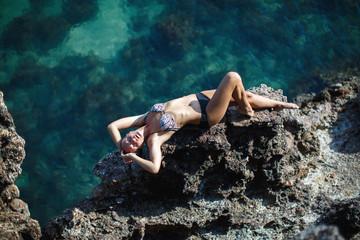 Girl lying on coastal sea rocks. Well being healthy lifestyle