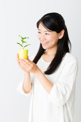 young asian woman holding green plant