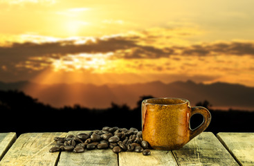 Coffee cup on wooden table and sunset background