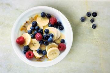 Cereal with blueberries, bananas, raspberries on white granite