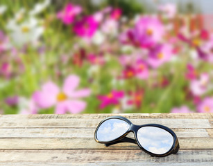 Clear sky in eyeglasses on the wooden table over blurred backgro