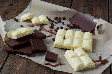 Pieces of white and dark chocolate on paper