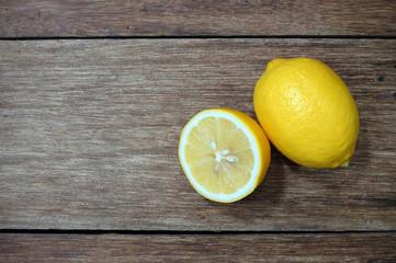 Freshly cut half and whole lemons on wood background