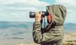 Hiker looking in binoculars in the mountains